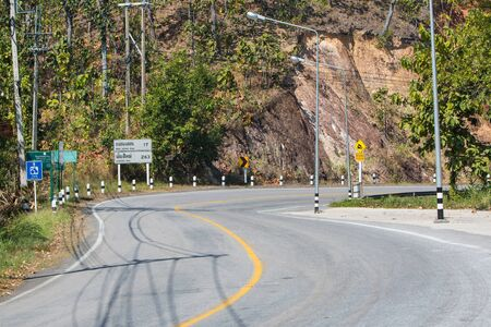steep: Curved and steep downhill road with road sign in Thailand Stock Photo