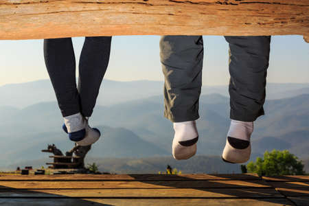 dangle: Two people sit on wooden seat and dangle their legs while looking to the nature