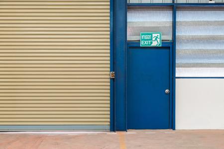 motorizado: puerta de salida de acero junto a la persiana motorizada de la f�brica, palabra tailandesa en la se�al de salida de medio de salida Foto de archivo