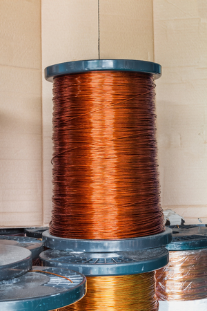 Round enameled copper wire or magnet wire in spool packaging, used for transformer manufacturing
