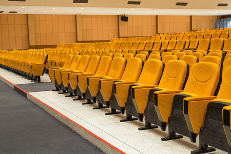 Empty conference hall with orange armchairs