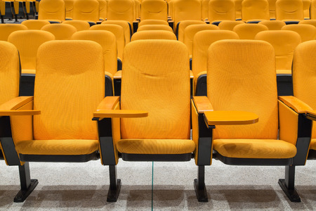 chief executive officer: Orange armchairs with folding table for writing in the conference hall Stock Photo