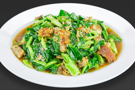 Gerecht van geroerbakte Kai-Lan (Chinese boerenkool) met knapperig varkensvlees