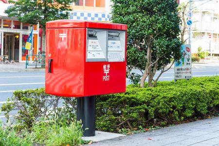 TOKYO, JAPAN - 12 OCTOBER 2016 - Red modern postbox installed in public beside the walkway in Tokyo, Japan.