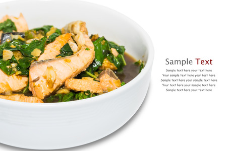 Close up of spicy fried salmon with holy basil (tulasi) leaves, isolated on white background with clipping path, with sample text