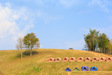Dome tents on camping site on the mountain at Doi Samer Dao in Nan province, Thailand, evening sunlight