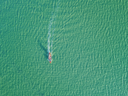Aerial view from drone of fishing boat moving in the sea, minimalist photography