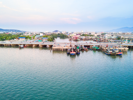 Aerial view of fishing boats pier at Tha Ruea Phli with Chonburi city in background, Thailand