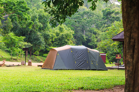 Family tent at campsite in national park, Thailand, Thai word on the signpost means Do not make fire