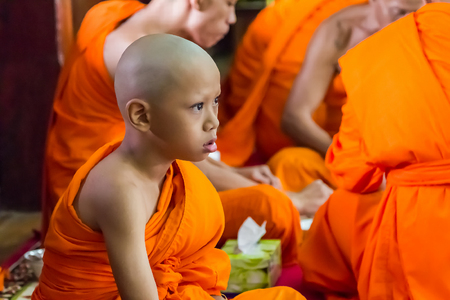 AYUTTHAYA, THAILAND - 08 OCTOBER 2017 - Unidentified Buddhist novice and monks in merit making (offering food to monks and novice) at temple in Ayutthaya province, Thailand