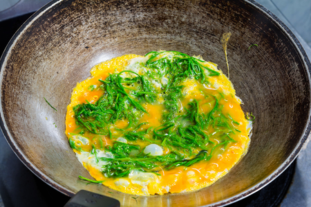 Climbing wattle (Cha-om) omelette, cooking in the pan