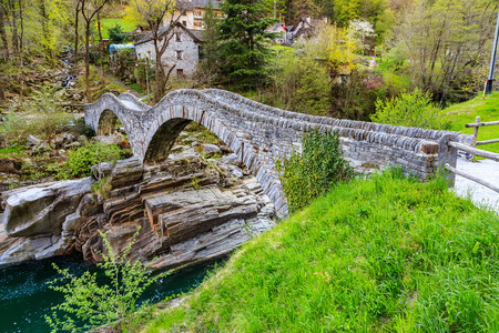 Two arches stone bridge soars over turquoise water stream of Valle Verzasca named Ponte dei Salti in canton of Ticino, Switzerland