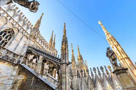 Wide angle worms eye view of Gothic architecture and art on the roof of Milan Cathedral (Duomo di Milano), Italy