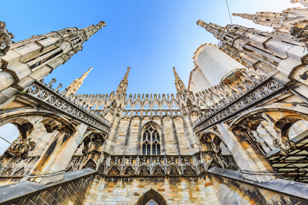 Wide angle worms eye view of the roof of Milan Cathedral (Duomo di Milano) with Gothic pinnacles in blue sky
