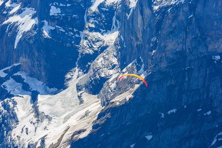 GRINDELWALD, SWITZERLAND - 24 APRIL 2018 - Unidentified couple glide with paramotor from Grindelwald First into the air of Jungfrau Region valley Editorial