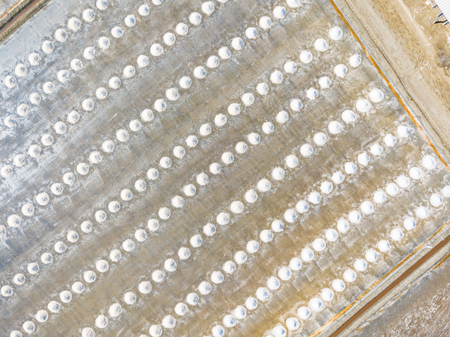 Aerial view form camera drone of gathered piles of sea salt after evaporation of brine in shallow saltpans or pools under sun and wind Imagens