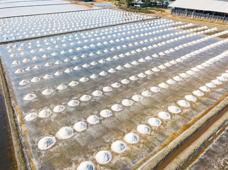 Aerial view from camera drone of sea salt farms, producing sea salt by filling the brine in the shallow pan and let it evaporate under sun and wind