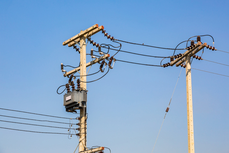 Electrical energy transfer to end users through distribution transformer on concrete pole changing high voltage to low voltage Reklamní fotografie