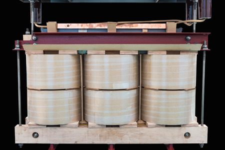 Internal active parts (core and coils) of three phase distribution oil immersed transformer during in production line, isolated on black background with clipping path