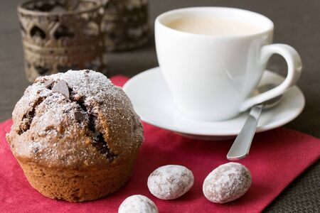 Closeup of Christmas decorated chocolated muffin in brown red colors and a coffee cup in the background. photo