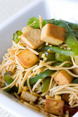 Closeup of fried noodles with tofu, coriander and green pepper. photo