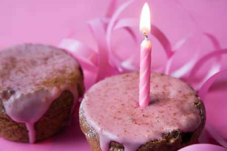 Muffin with pink icing and a candle, suitable for birthday, Valentine Day or celebrate a jubilee photo