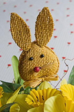 Selective focus image of an Easter still life with a bunny puppet and yellow flowers. photo