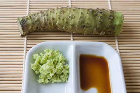 Selective focus imaga of grated fresh wasabi root also called Japanese horseradish on a bamboo mat with soy sauce.