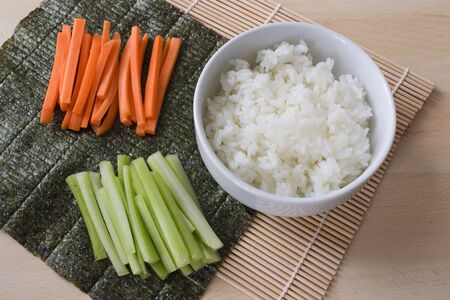 bamboo mat: Ingredients for sushi: sliced carrots and celery, bowl with rice, nori and a bamboo mat on a work plate.