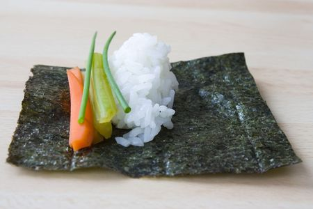 Ingredients for temaki sushi: sliced carrots, celery, rice and  a sheet of nori on a work plate