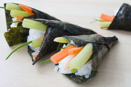 Selectieve aandacht afbeelding van temakizushi gemaakt van gesneden wortelen, selderij, rijst en zeewier. Stockfoto