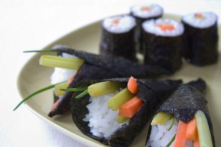 Selectieve aandacht foto van een gele plaat met verschillende soort sushi, zoals maki en temaki