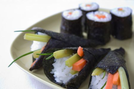Selective focus image of a yellow plate with different kind of sushi, like maki and temaki