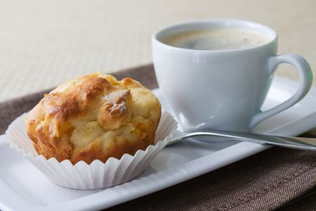 Selective focus image of a mango muffin with a cup of espresso on a white plate