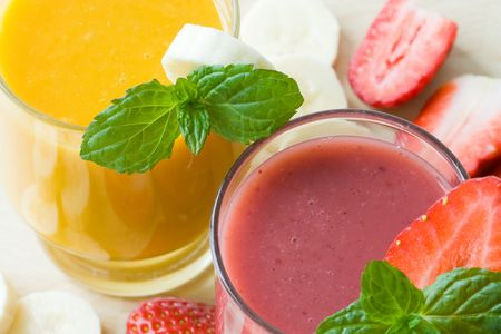 Selective focus image of two smoothies in red and yellow colors.