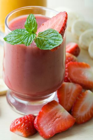 Selective focus image of a smoothie with strawberries and mint.