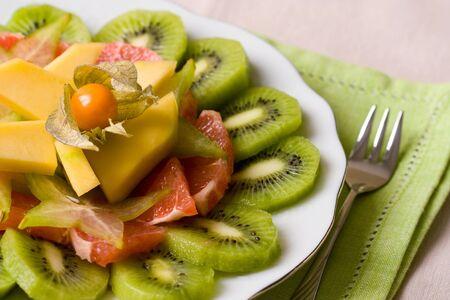 Selective focus image of a tropical fruit salad made from grapefruits, mango, physalis and kiwi fruits. photo