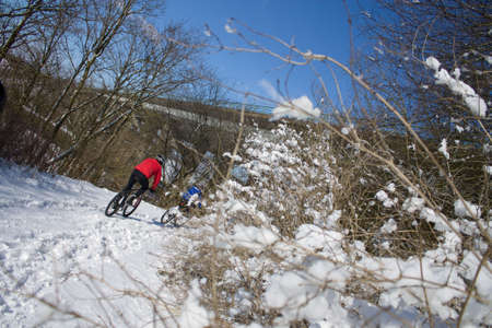 Sportsmen cycling in a landscape with snow on a sunny day Stock Photo