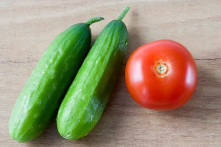 english cucumber: Selective image of small English cucumber with a tomato on a wooden countertop
