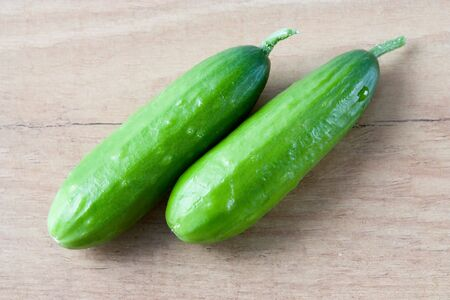 english cucumber: Selective image of small English cucumbers on a wooden countertop Stock Photo