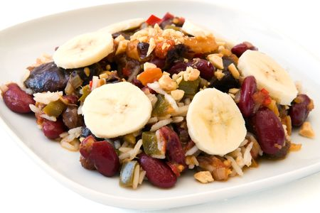 dried plums: Traditional South African vegetarian curry made from kidney beans and dried fruits, served with rice, bananas and peanuts as cut out image. Stock Photo