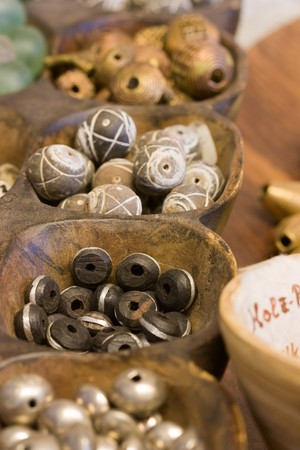 Selective focus image of different African pearls made from wood with decorative pattern.