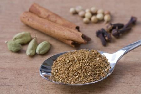 Selectieve aandacht beeld van de overvloeiing Garam Masala en zijn ingrediënten zoals koriander, kardemom, kaneel en kruid nagel.  Stockfoto