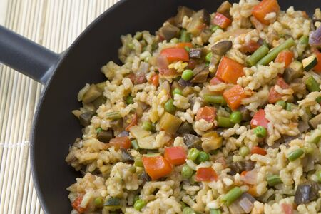 Vegetarian rice dish made from pepper, tomatoes, beans, peas, aubergines, courgette and onion which is in Spain also called paella. photo