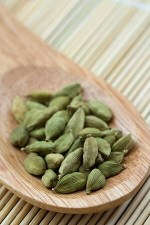 cardamum: Close-up image of cardmom seeds placed in a wooden spoon.