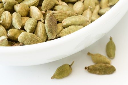 cardamum: Selective focus image of cardamom in a white bowl with copy space.