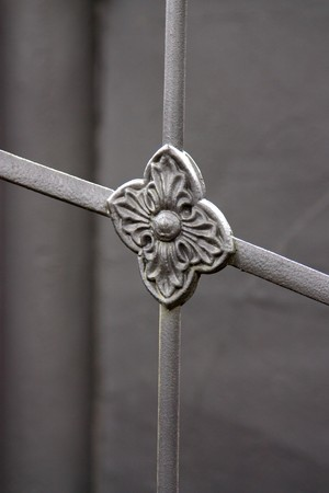 Selective focus image of a wrought ironwork showing a decorative flower which belongs to a gate. photo