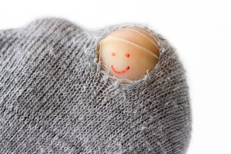 optimistic: Close-up image of a sock with a hole and a smiley on the toenail.