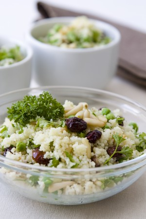 Selective focus image of a vegetarian couscous salad with cranberries and peas.