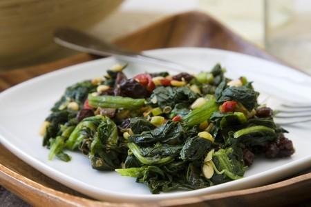 Indische Gekookte spinazie met rozijnen, pijnboompitten en rode peper.